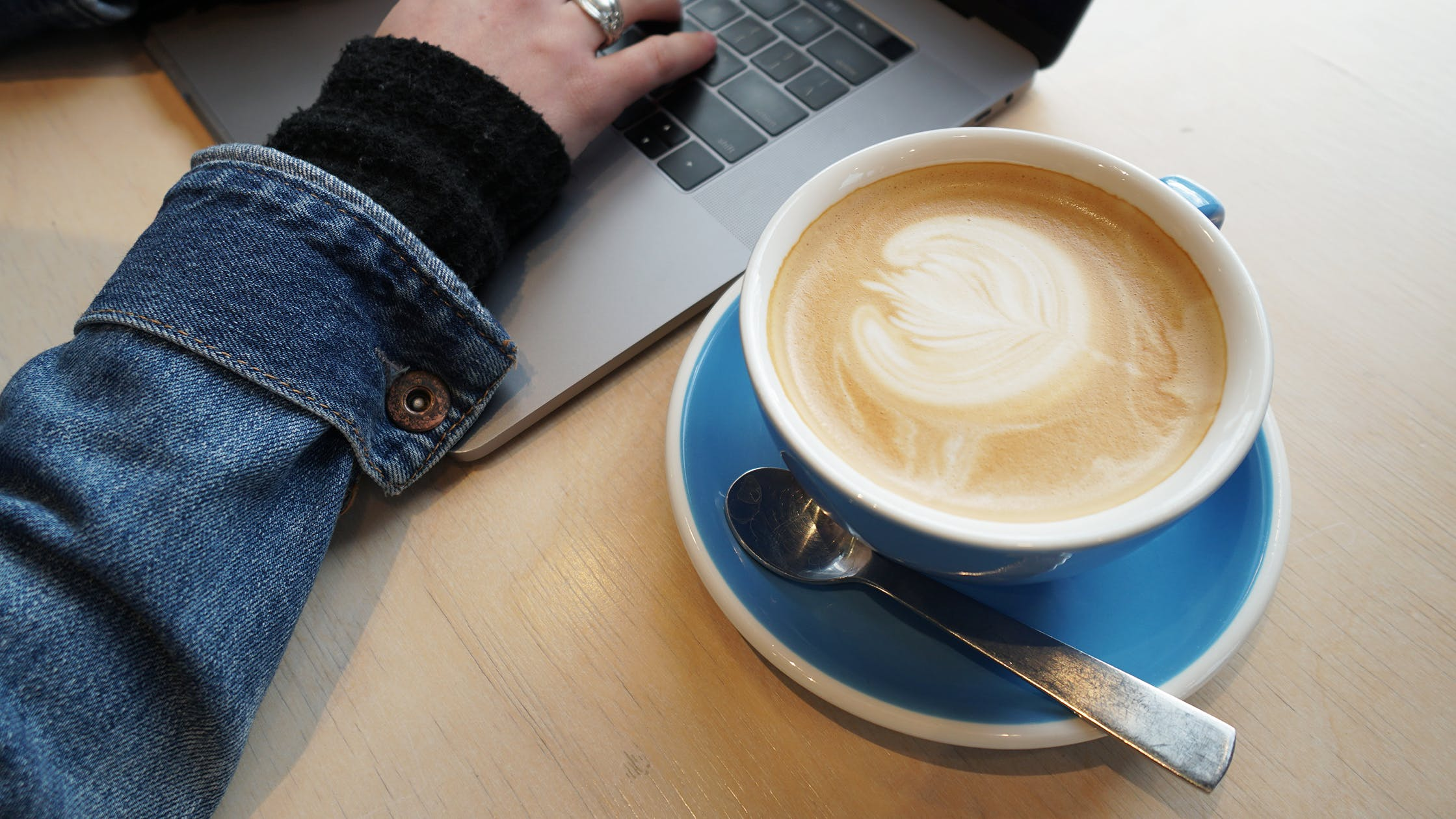 Working Remotely At A Local Coffee Shop With Ordered Beverage