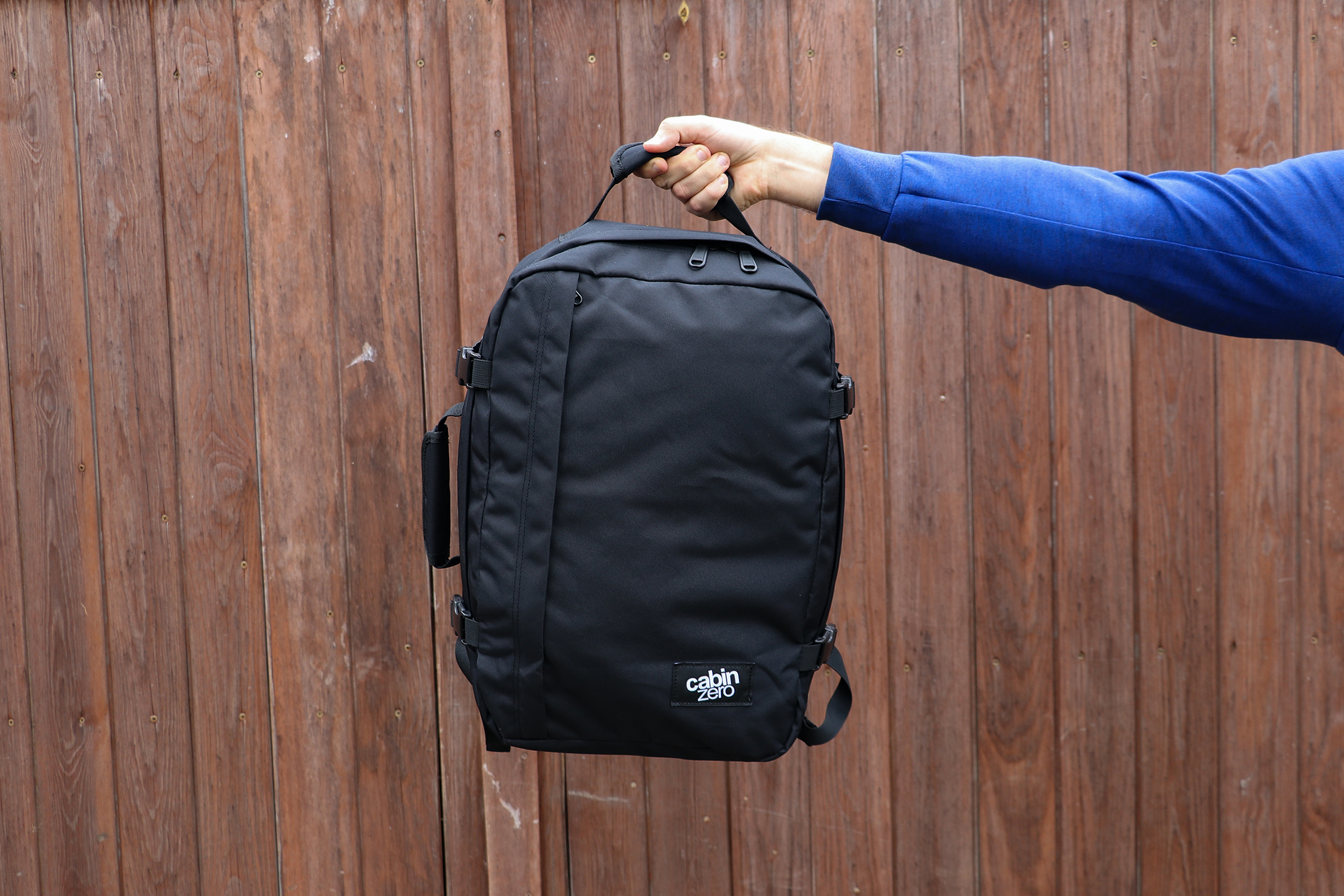Holding The CabinZero Classic Travel Backpack With The Top Handle