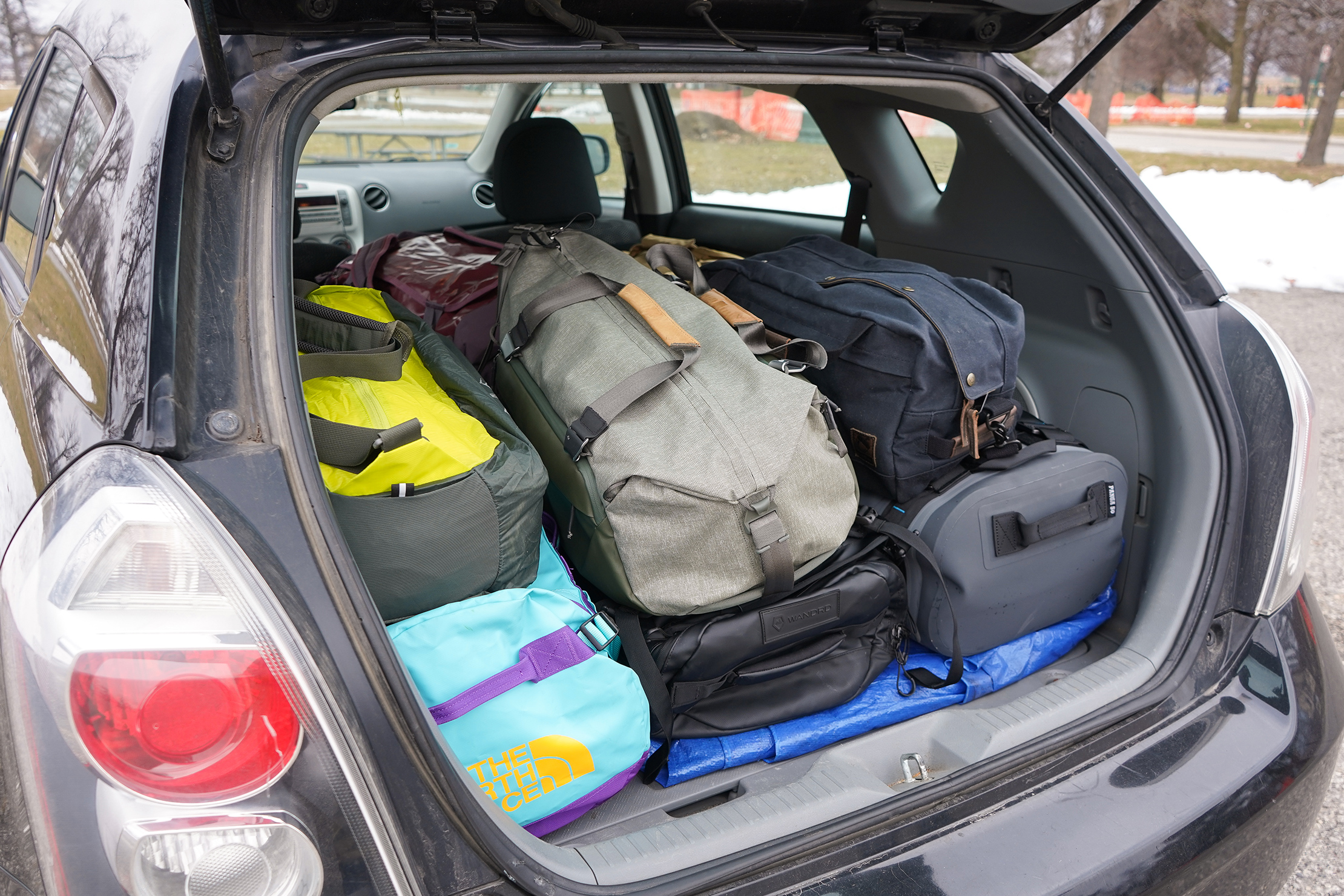 Duffle Bags Stacked In The Trunk Of A Car