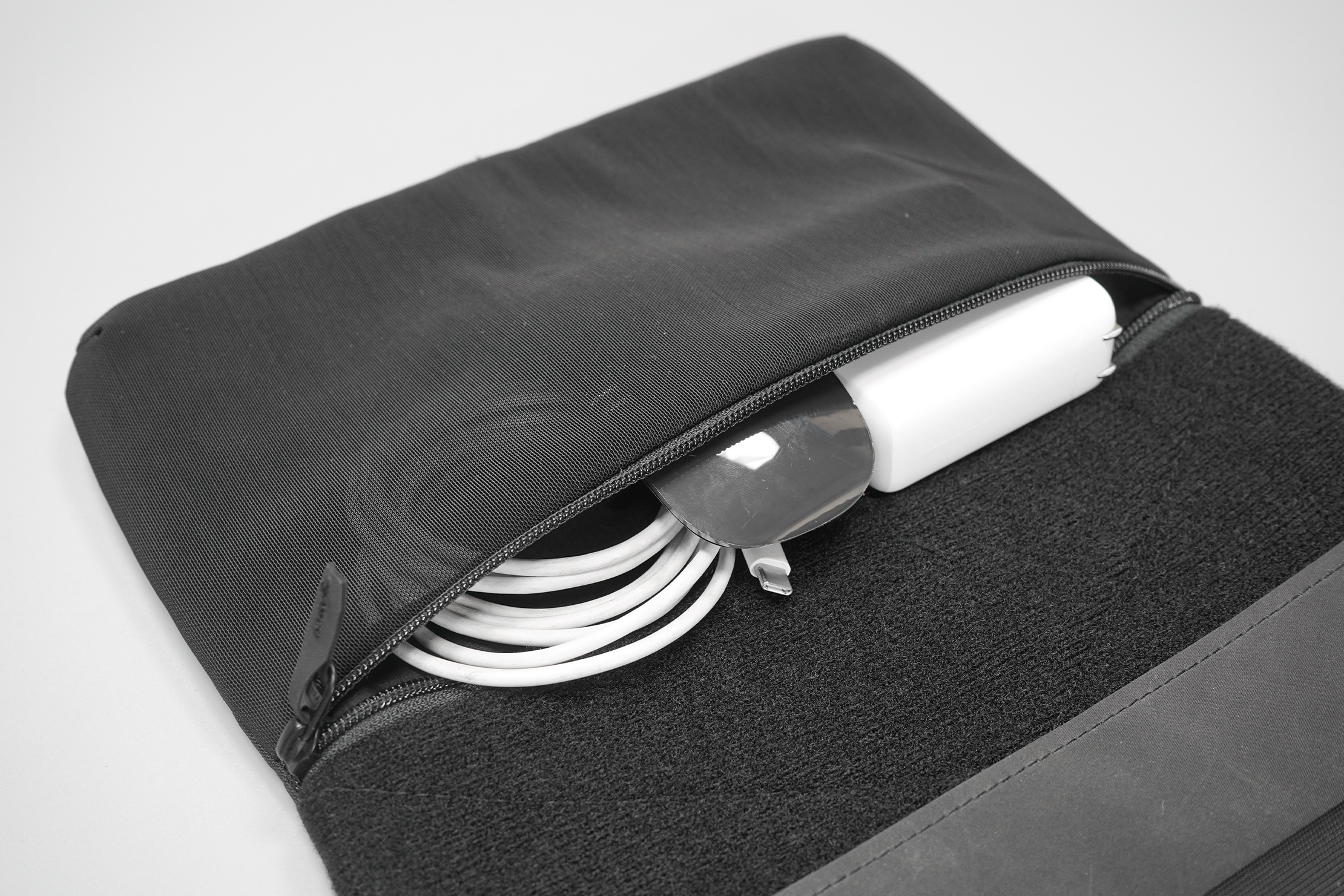 Matador Laptop Base Layer   The mesh pocket, filled with laptop accessories.