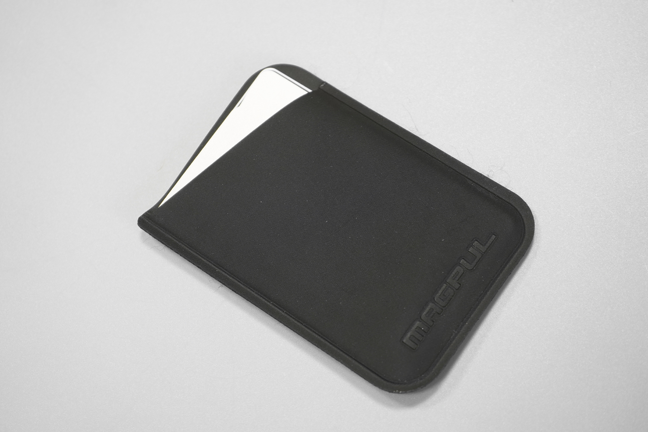 Magpul DAKA Micro Wallet   The debossed logo and polymer fabric, with some fraying at the edges.